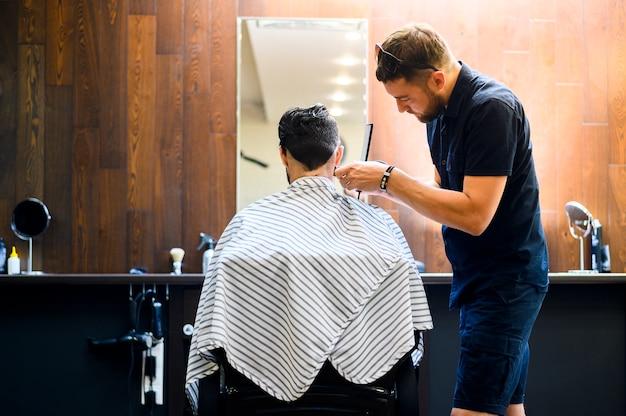 Вид сзади парикмахер стрижка волос клиента