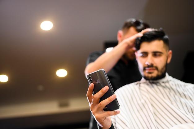Костюм низкого угла в парикмахерской смотря телефон с космосом экземпляра