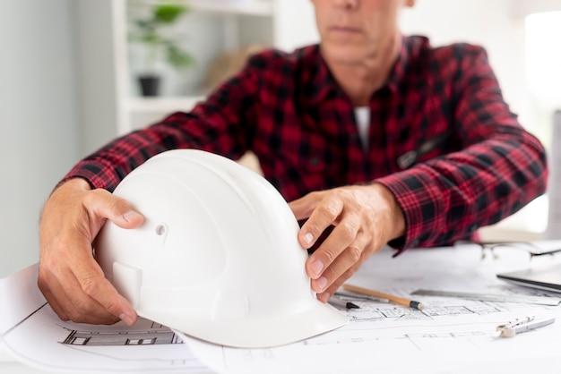 Архитектор держит свой защитный шлем