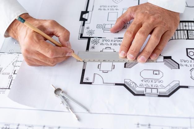 彼のプロジェクトのクローズアップに定規を使用して建築家