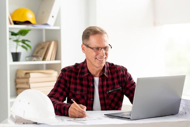 Архитектор работает над ноутбуком для своего проекта