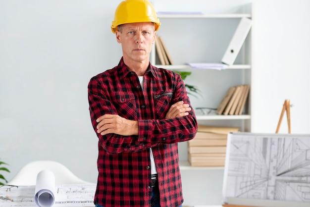 Серьезный архитектор в защитном шлеме смотрит в камеру
