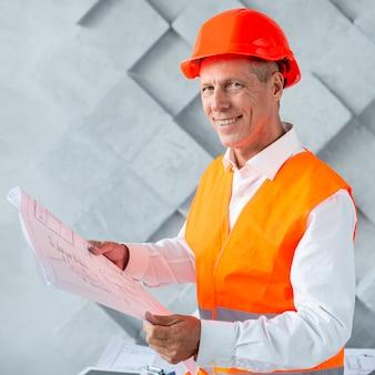 Архитектор в защитном шлеме смотрит в камеру