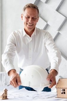 Архитектор ставит защитный шлем на стол