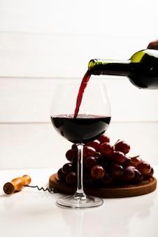 Вид спереди вина наливают в бокал
