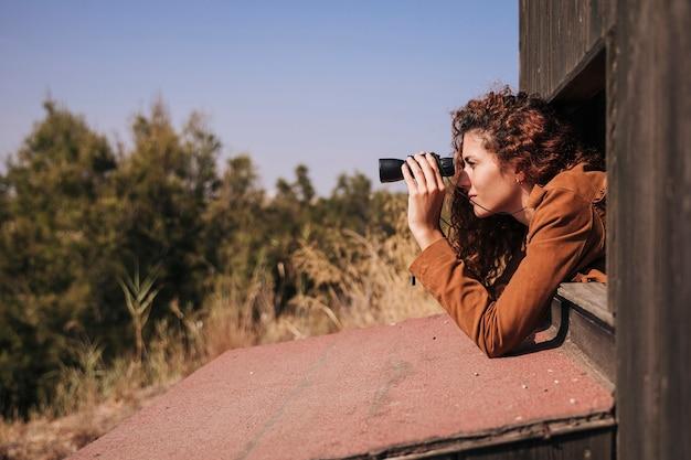 Боком рыжая женщина смотрит в бинокль