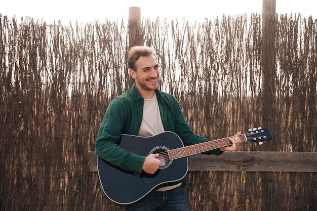 正面の笑みを浮かべて男がギターを弾く