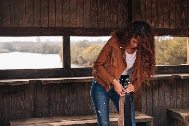 フロントビュー女性、ギターのチューニング