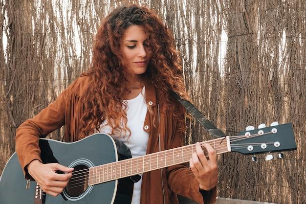ミディアムショットの女性がギターを弾く