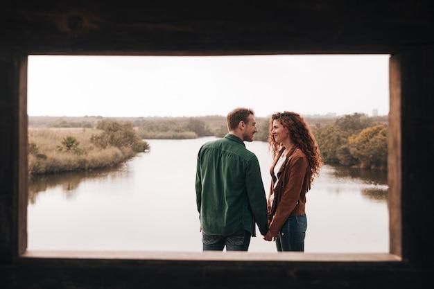 Счастливая пара, держась за руки рядом с прудом
