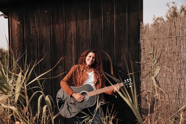 フロントビュー幸せな女、ギターを弾く