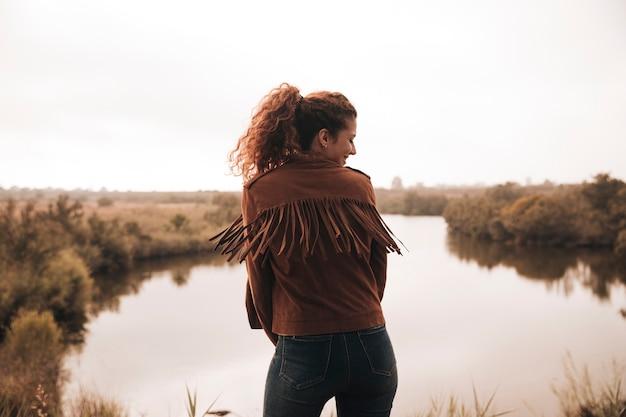 Вид сзади женщина позирует рядом с прудом
