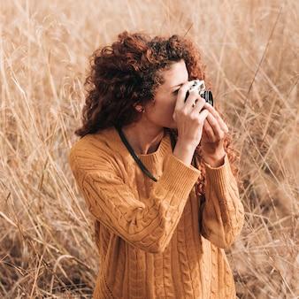 麦畑で写真を撮る女性