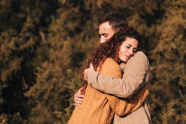 Боком обниматься пара на открытом воздухе