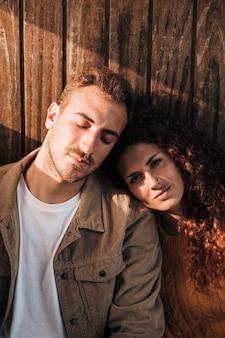 Пара вид спереди расслабляющий с деревянными фоне