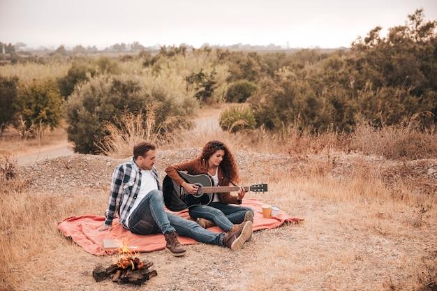 キャンプの火の横にある屋外でリラックスしたカップル