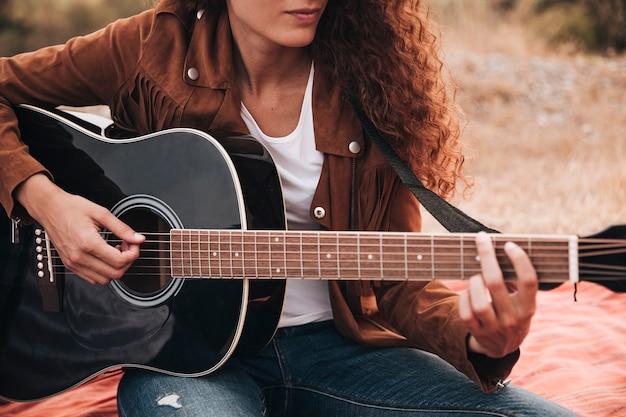 正面の女性がギターを弾く