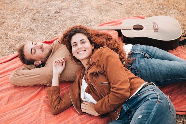 Высокий вид пара лежит на одеяле на открытом воздухе