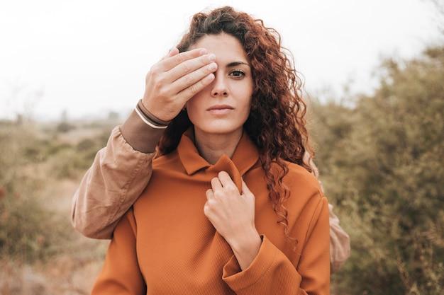 Вид спереди человека, охватывающего женский глаз