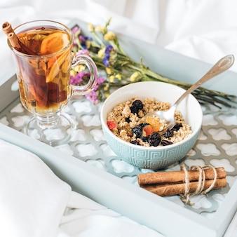 ミューズリーと紅茶が付いているベッドでの朝食