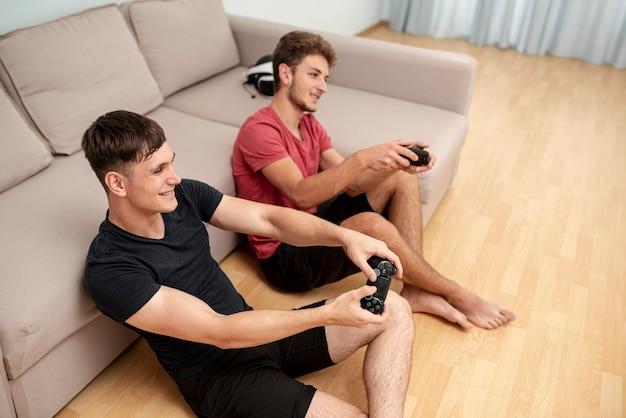 Высокий угол парни играют с контроллерами