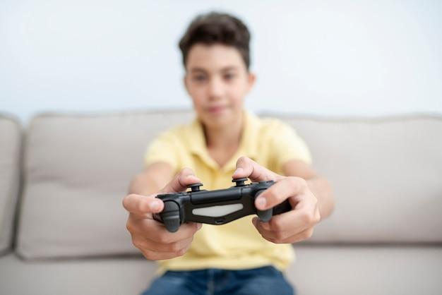 Вид спереди малыш с контроллером на диване