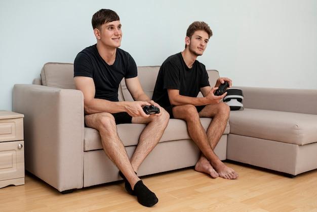 Полный выстрел парни играют на диване