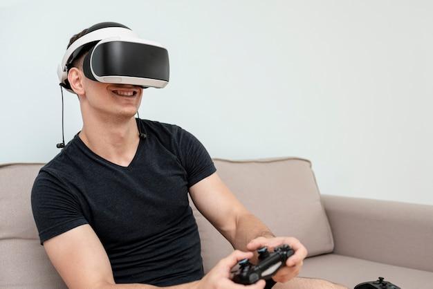 Вид сбоку парень с очками и контроллером