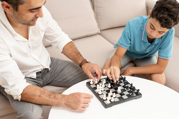 Высокий угол взрослый и ребенок играет в шахматы
