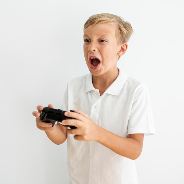 Боковой вид блондинка ребенок играет в помещении