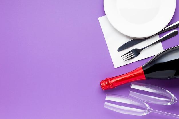 Вид сверху бутылка вина, стаканы и тарелка