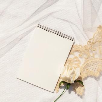 空のメモ帳のクローズアップと女性の結婚式のアレンジメント
