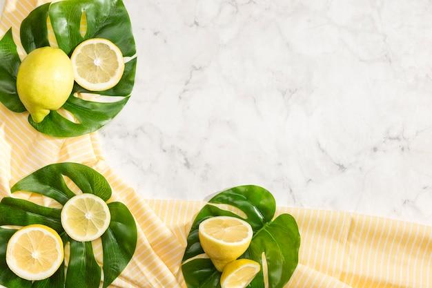 Симпатичная композиция лимонов на листьях монстера