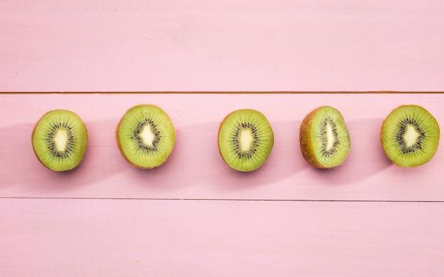 ピンクの背景にキウイフルーツの半分
