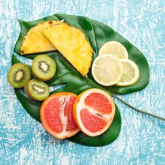 ジューシーなエキゾチックなフルーツとモンステラの葉