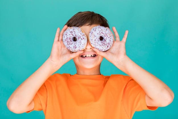 ドーナツで彼の目を覆っている笑顔の少年