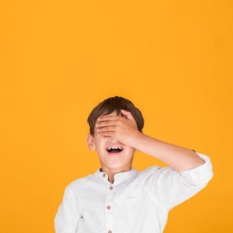 コピースペースで彼の目を覆っている小さな子供