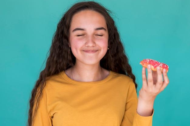 Маленькая девочка наслаждается глазированным пончиком