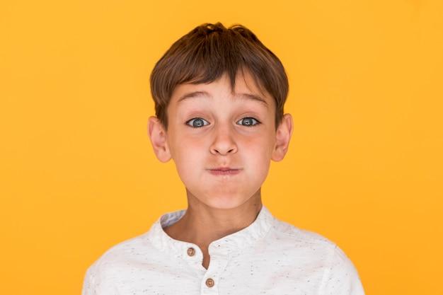 Маленький мальчик делает глупое лицо