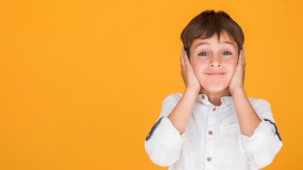 コピースペースで彼の耳を覆う少年