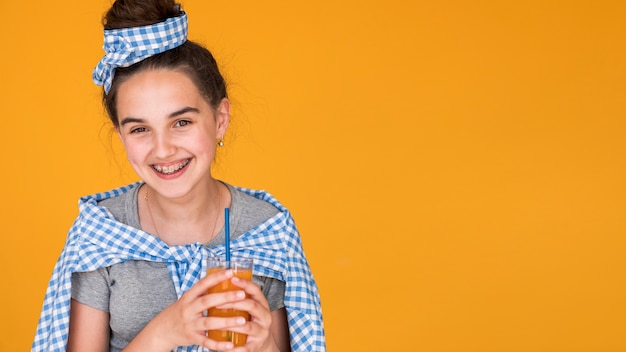 彼女のオレンジジュースを楽しんでいる笑顔の女の子