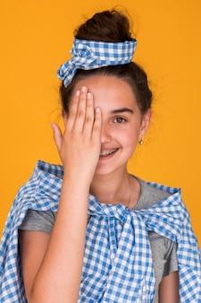 Стильная девушка закрывает один глаз