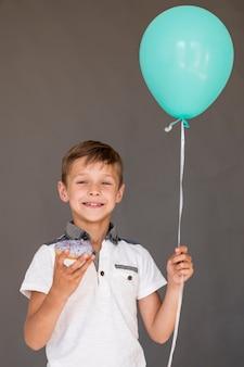 Мальчик держит глазированный пончик и воздушный шар