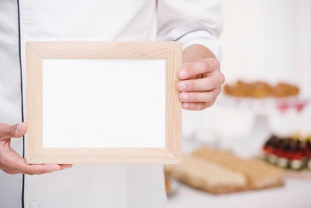 モックアップで木製フレームを提示するシェフ