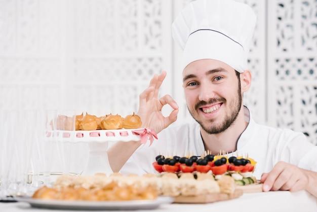 Счастливый шеф-повар, представляя еду на столе