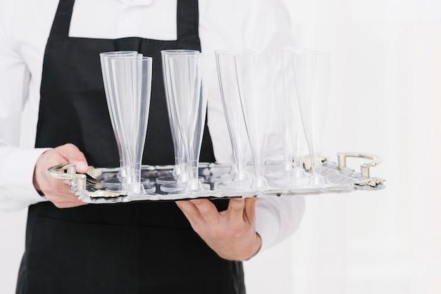 Официант держит пустые стаканы на подносе