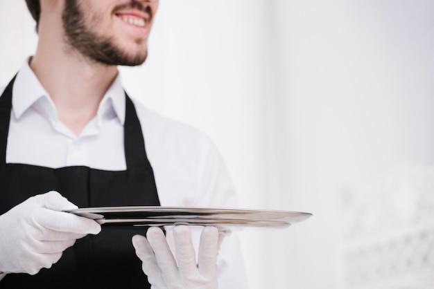 Бородатый официант держит металлический поднос
