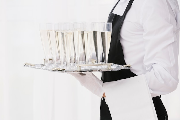 Слуга держит поднос со стаканами