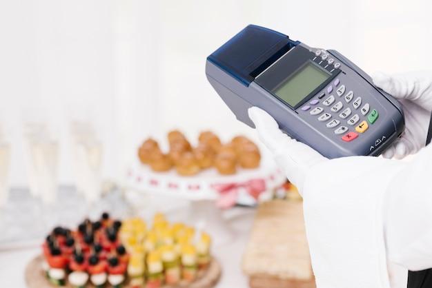 Крупным планом официант держит телефон