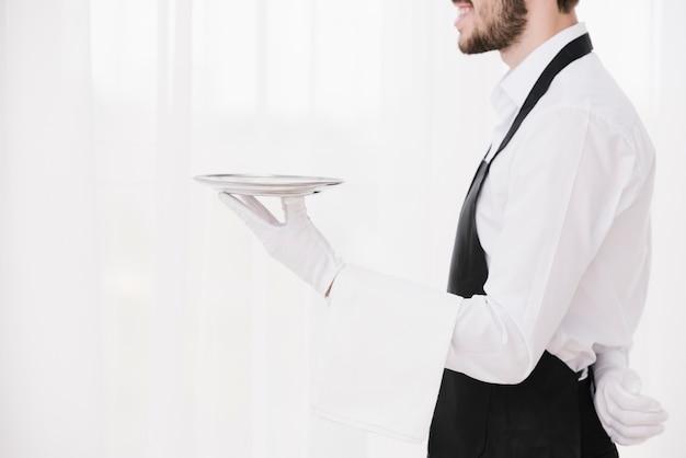 Боком официант держит металлическую пластину